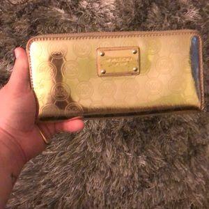 Michael Kors Bags - Gold monogrammed Michael Kors wallet